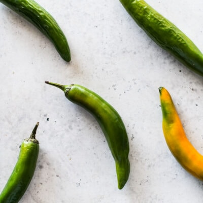Serrano peppers on a white table.