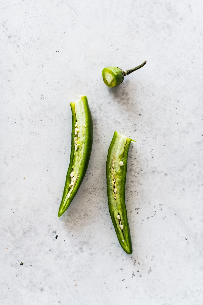 A serrano pepper sliced in half to reveal the veins and seeds.