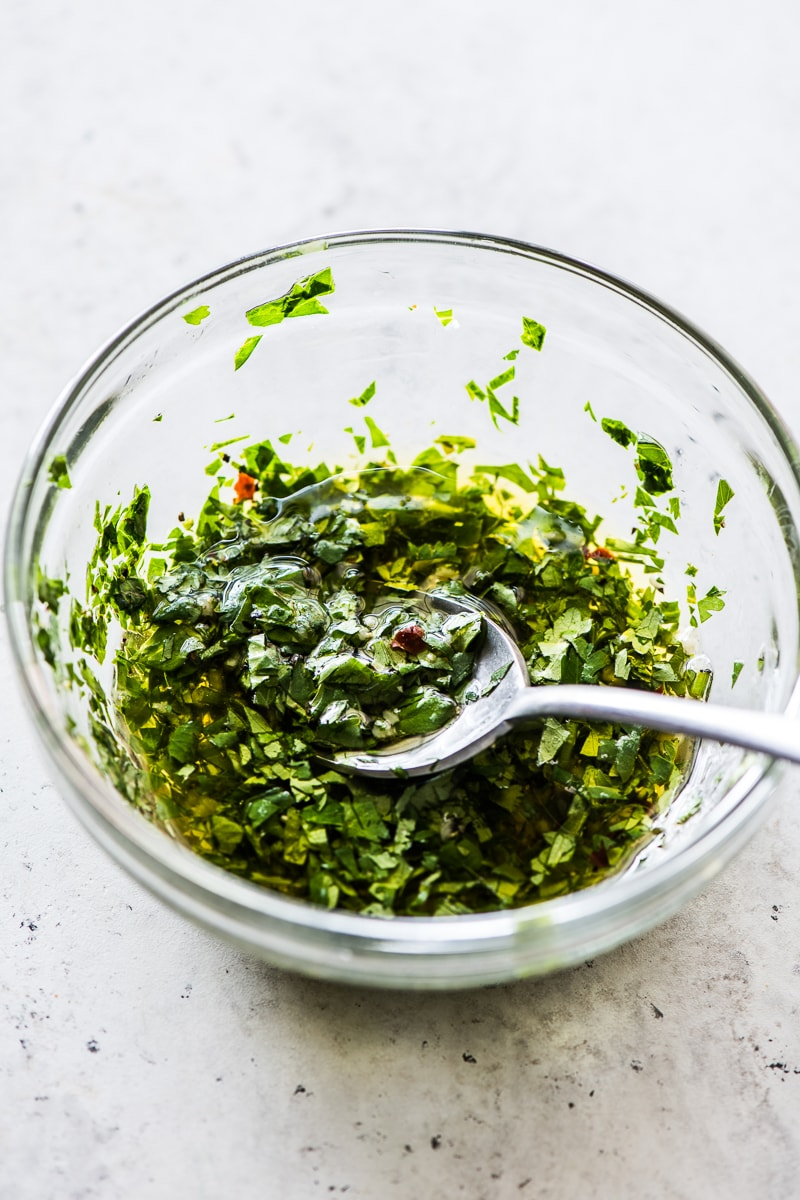 A small bowl filled with an herb sauce made from cilantro and parsley.