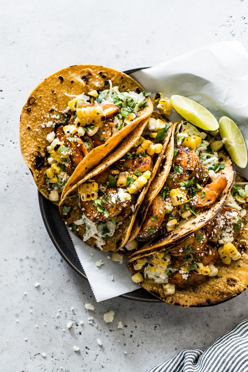 Grilled shrimp tacos on a plate topped with cotija cheese and cilantro.