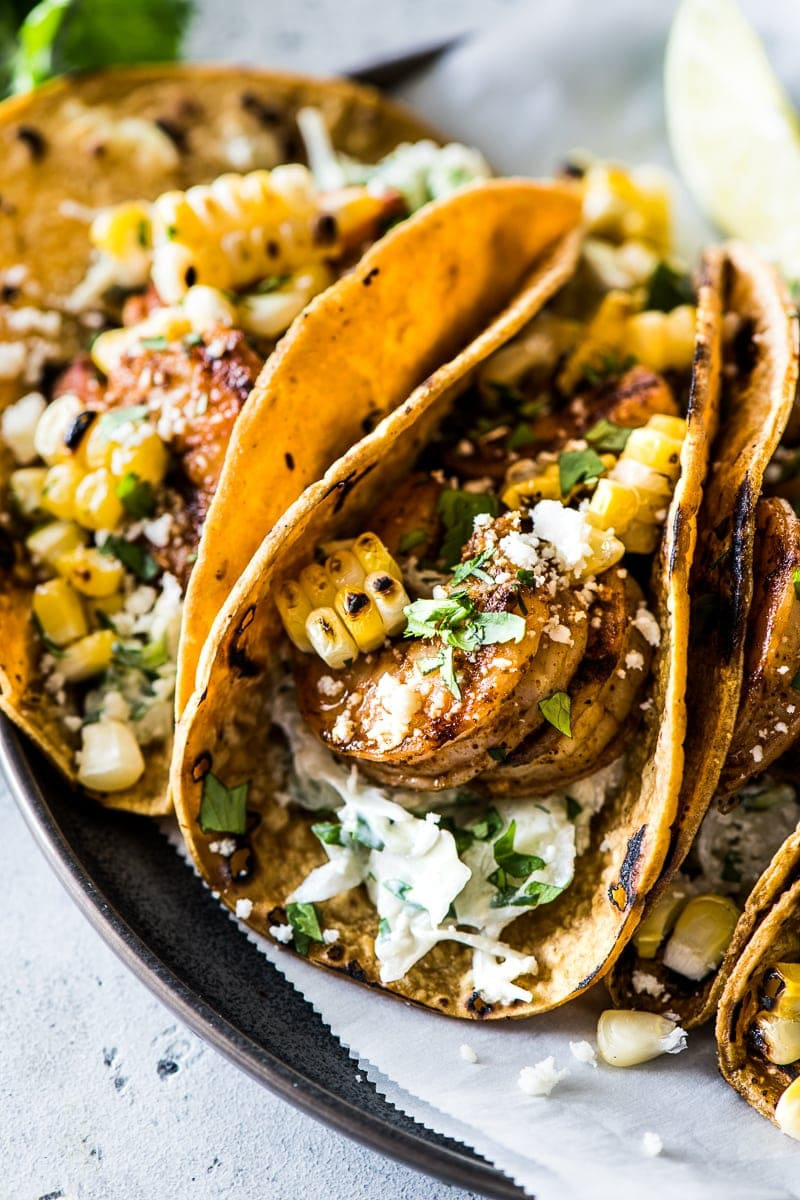 Grilled shrimp tacos on a plate topped with cotija cheese, cilantro and grilled corn.