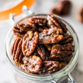 These candied pecans are easy to make on the stovetop - no need to turn on the oven! Crunchy, sweet and the perfect little snack, they're ready in under 10 minutes. Perfect for topping on salads and dessert, they even make a great holiday gift! #candiedpecans #holidays #pecans