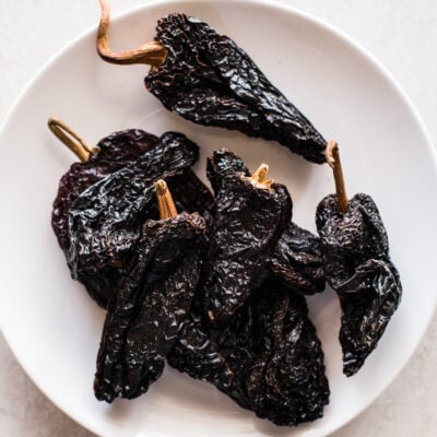 Dried ancho chile peppers on a white plate