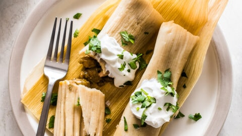 Chicken tamales made from an easy masa tamale dough and stuffed with tender pieces of chicken and green chile verde sauce. Great for serving a crowd or freezing and reheating for later! #tamales #chickentamales #glutenfree #mexicanfood