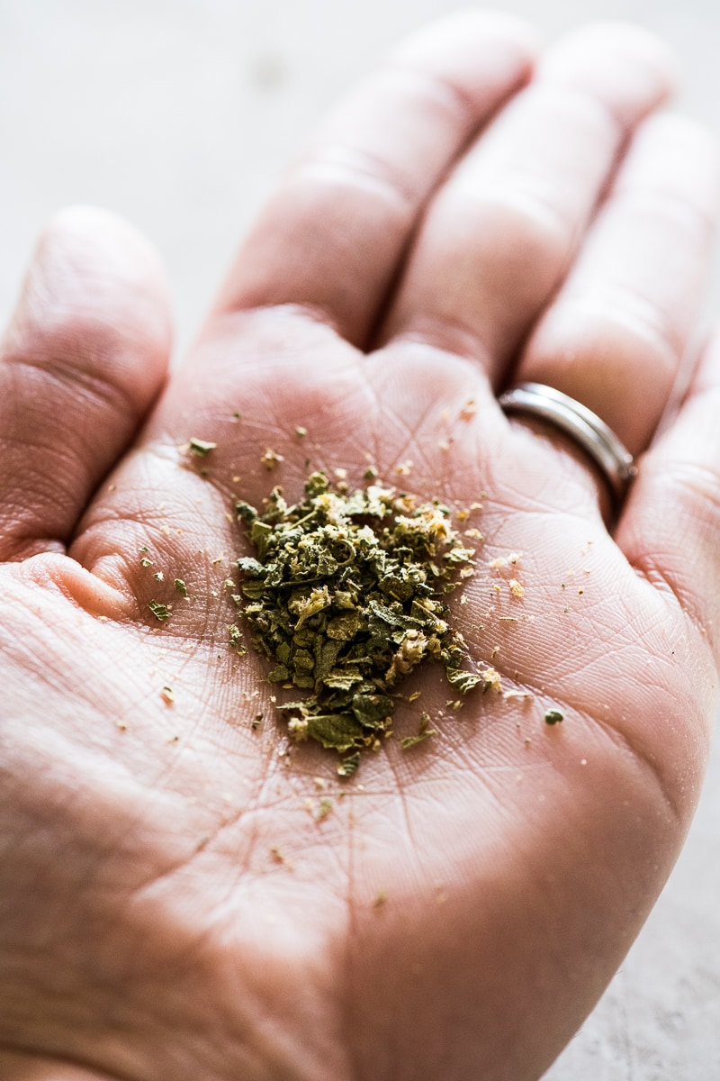 The palm of a hand holding Mexican oregano that has been rubbed and broken
