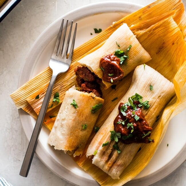 Pork Tamales with red chile sauce on corn husks.