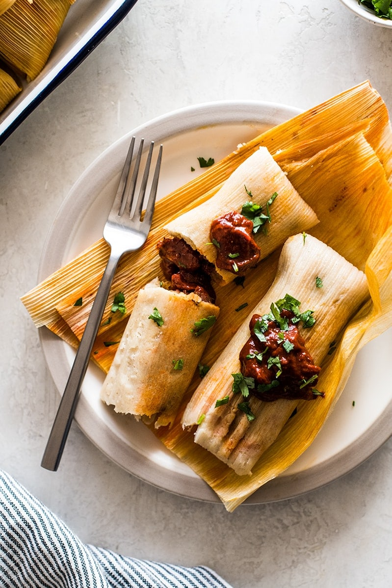 Pork tamales ready to eat on corn husks.