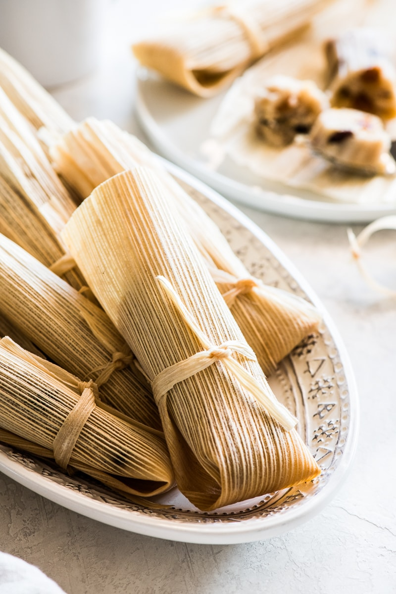 Sweet tamales in their corn husk ready to eat on a platter