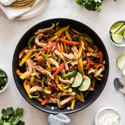 Turkey fajitas in a skillet with bell peppers and onions