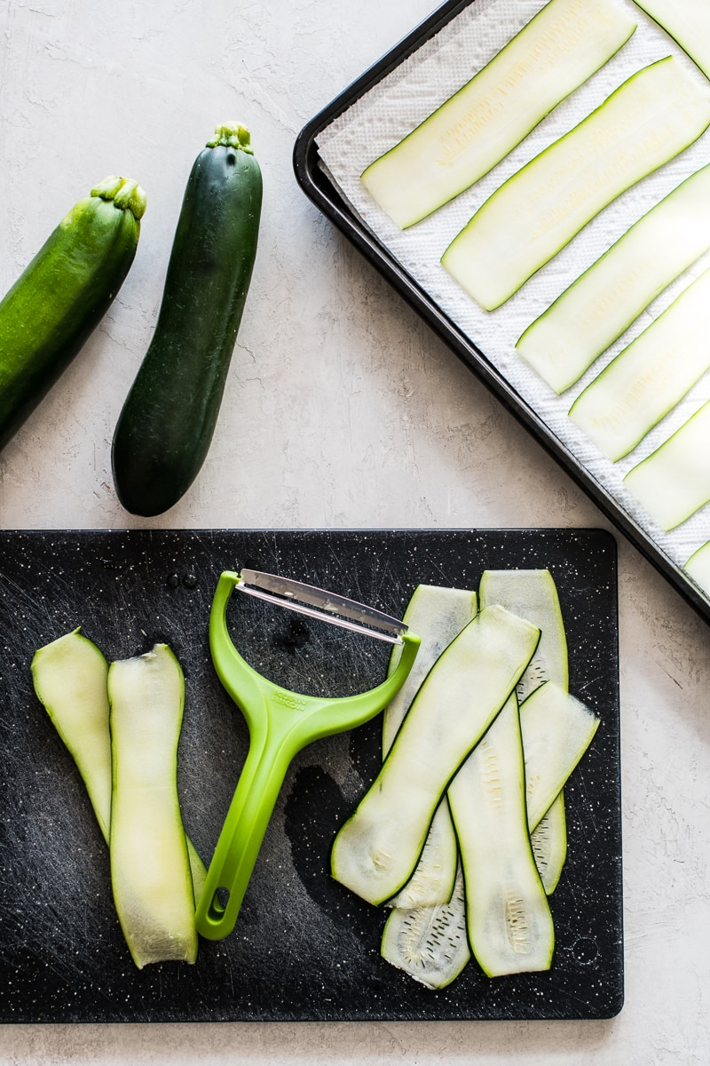 Thinly sliced zucchini on a cutting board