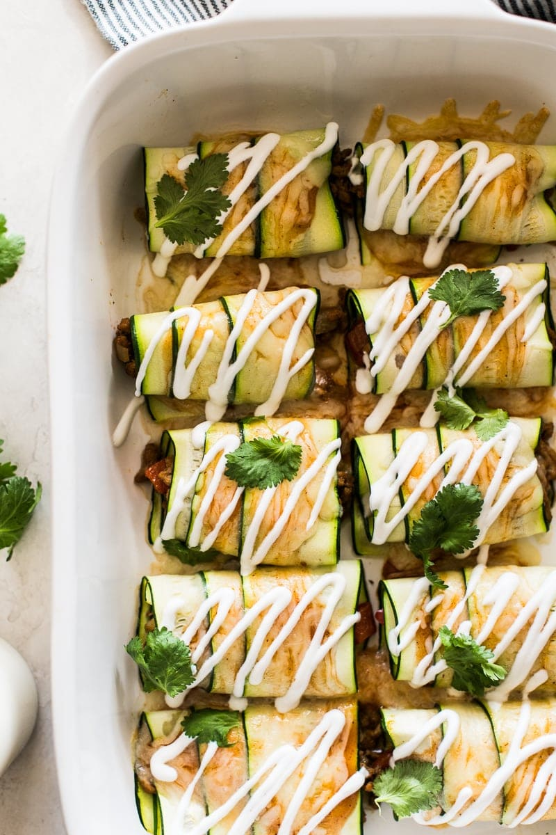 Zucchini enchiladas topped with sour cream and cilantro