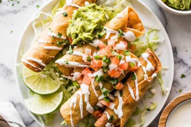 Chicken taquitos on a plate with shredded lettuce and pico de gallo.