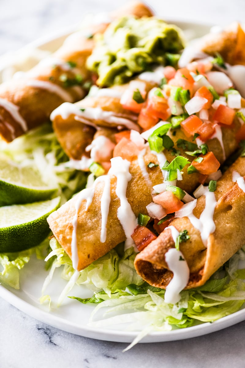 Crispy taquitos filled with chicken and topped with mexican toppings