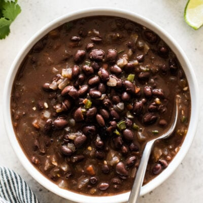 Cooked canned black beans with tomatoes, onions and garlic in a bowl.