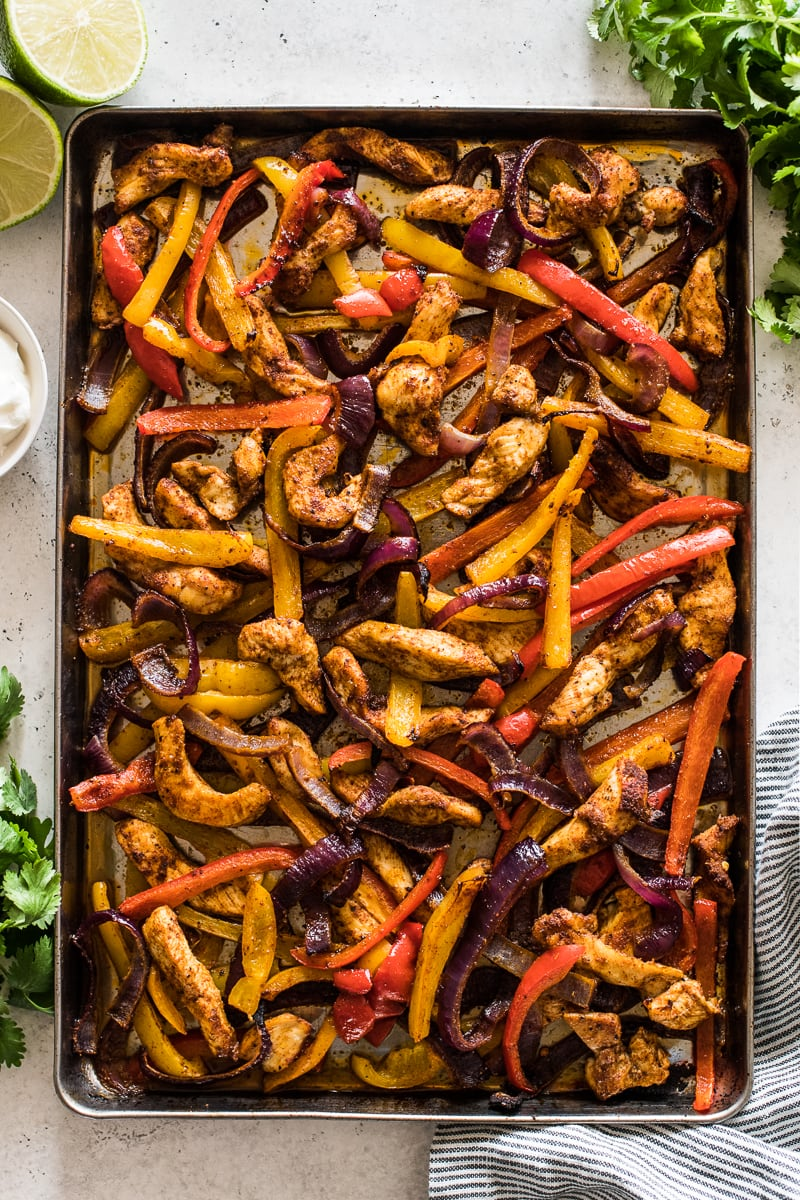 Sheet pan chicken fajitas with cilantro and lime wedges.