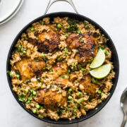 Arroz con pollo in a pan topped with cilantro and lime wedges.