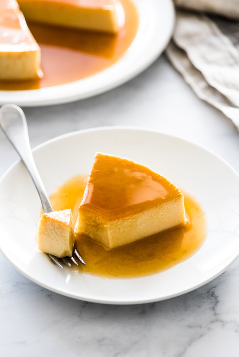A slice of flan on a plate with a fork