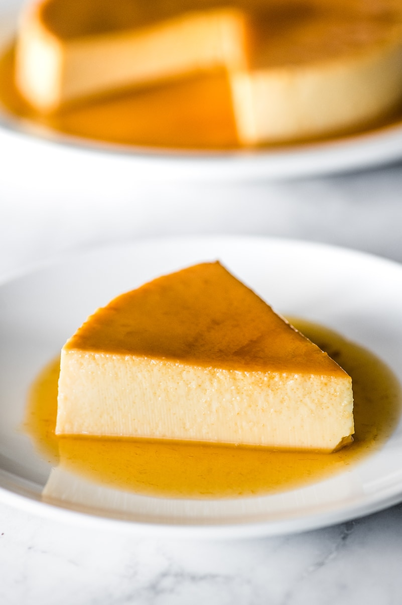A slice of flan on a plate with caramel