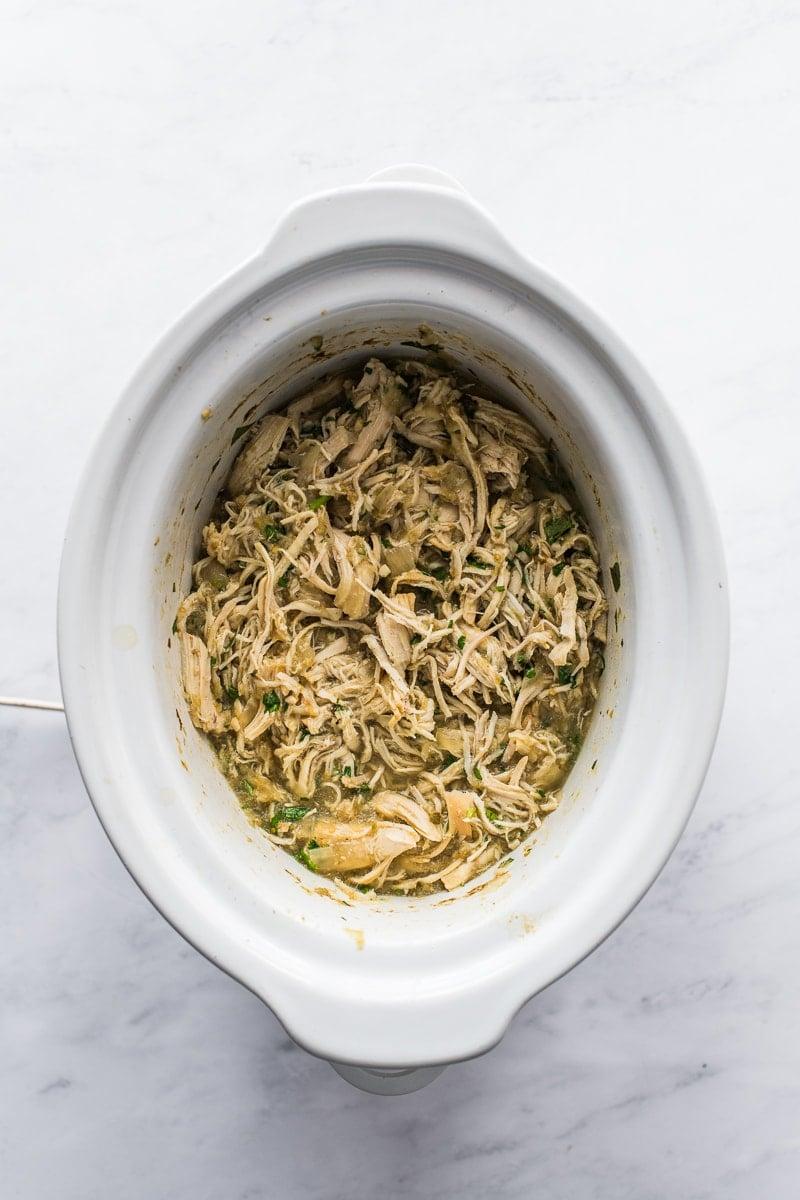 shredded salsa verde chicken in a slow cooker crock pot