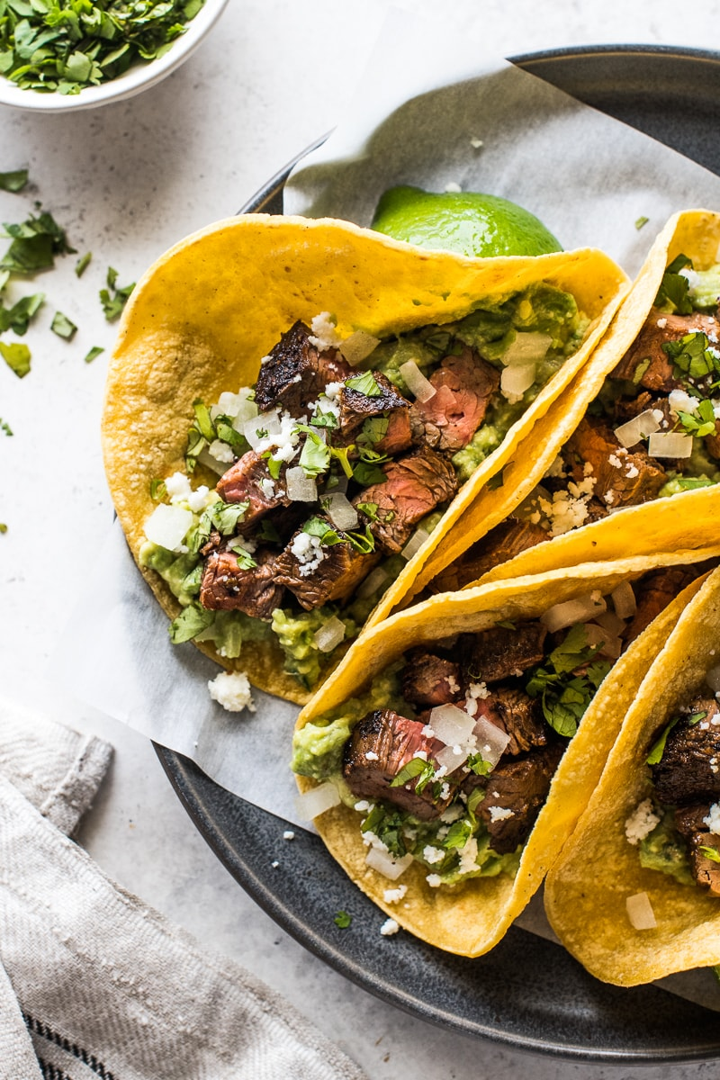 Carne Asada Tacos topped with cotija cheese, onions and cilantro.
