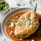 Chile relleno on a plate with red salsa.