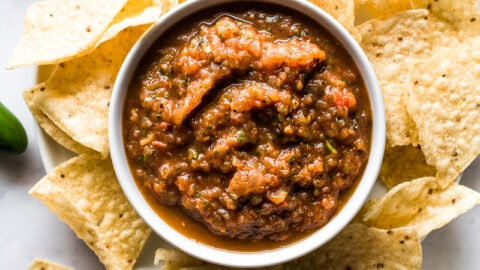 Roasted tomato salsa in a bowl surrounded by tortilla chips.
