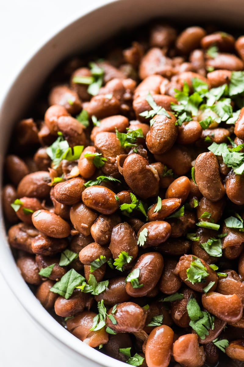 Tender instant pot pinto beans topped with cilantro.