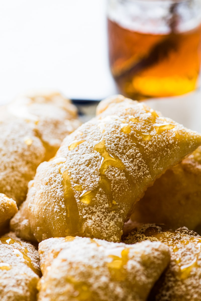 Sopapillas topped with powdered sugar and honey.