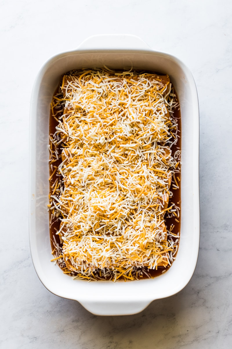 Chicken enchiladas topped with shredded cheese ready to be baked.
