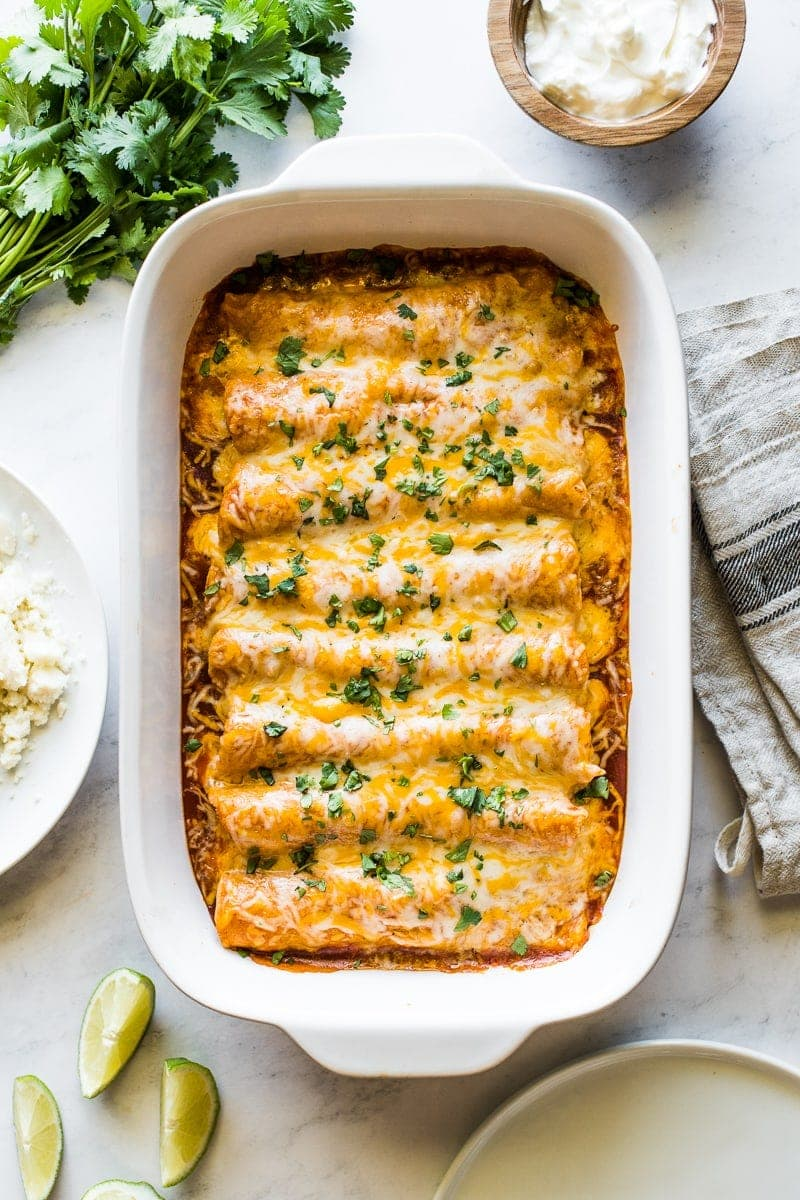 Chicken enchiladas in a baking dish topped with cilantro.
