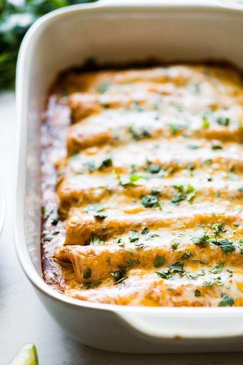 Cheesy chicken enchiladas with melted cheese in a baking dish.