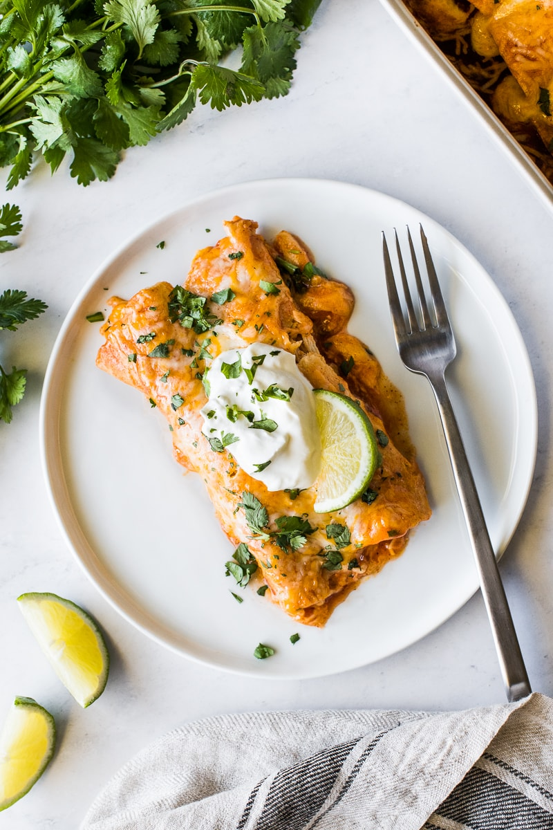 Chicken enchiladas on a plate topped with sour cream.