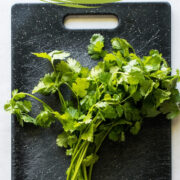 A bunch of cilantro on a cutting board