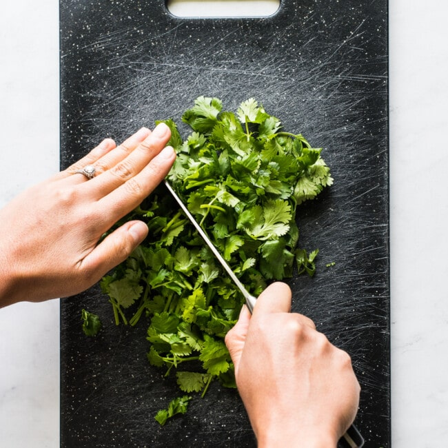 Two hands chopping cilantro on a cutting board.