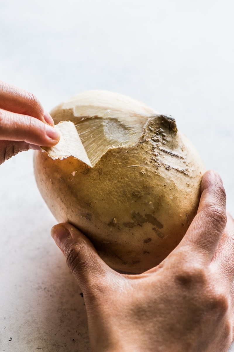 A jicama being peeled
