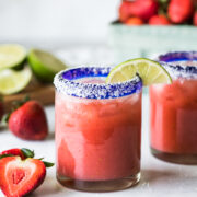 A strawberry margarita in a glass garnished with a lime.