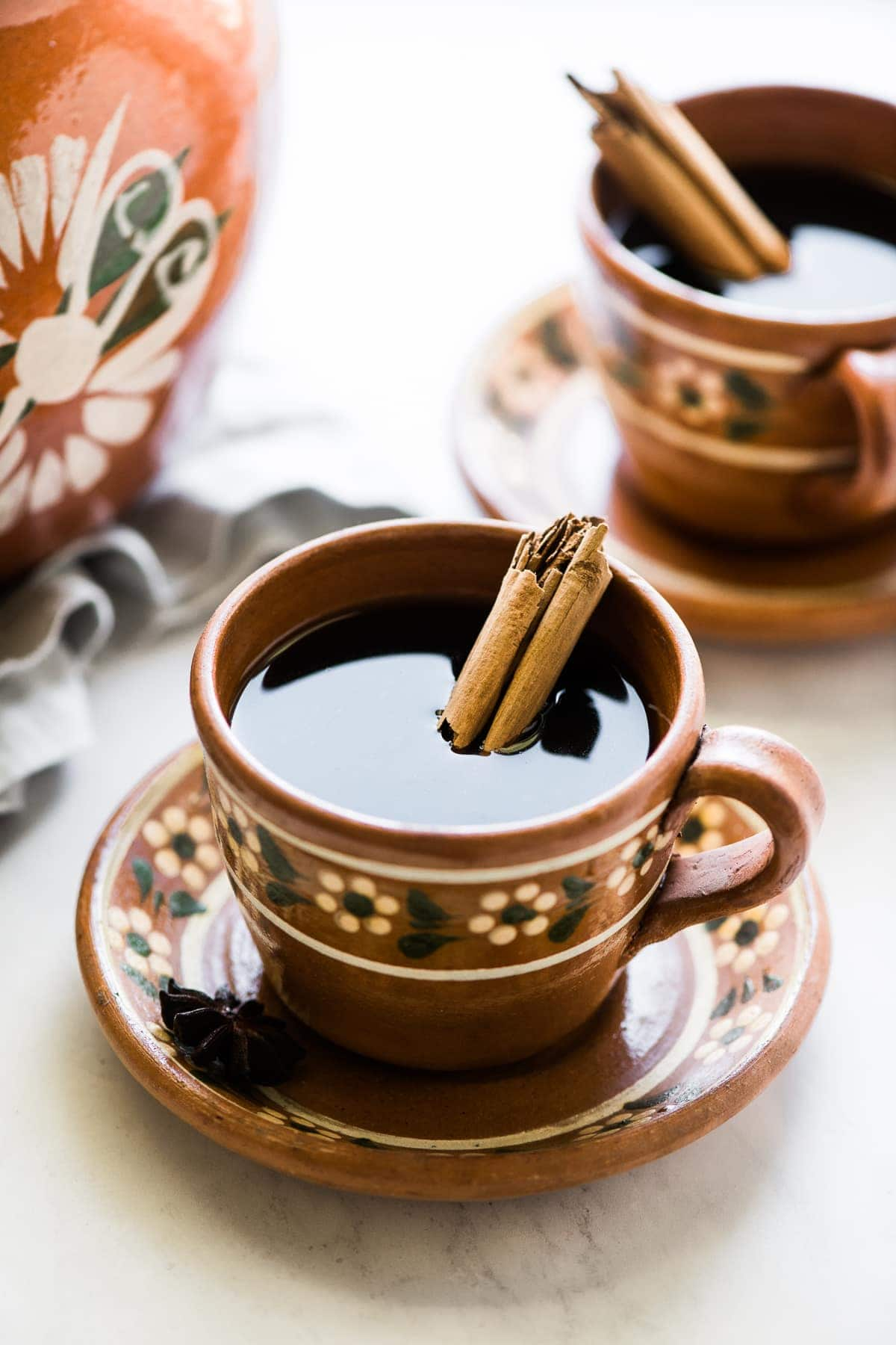 Cafe de olla (traditional Mexican coffee) in a mug with a cinnamon stick.