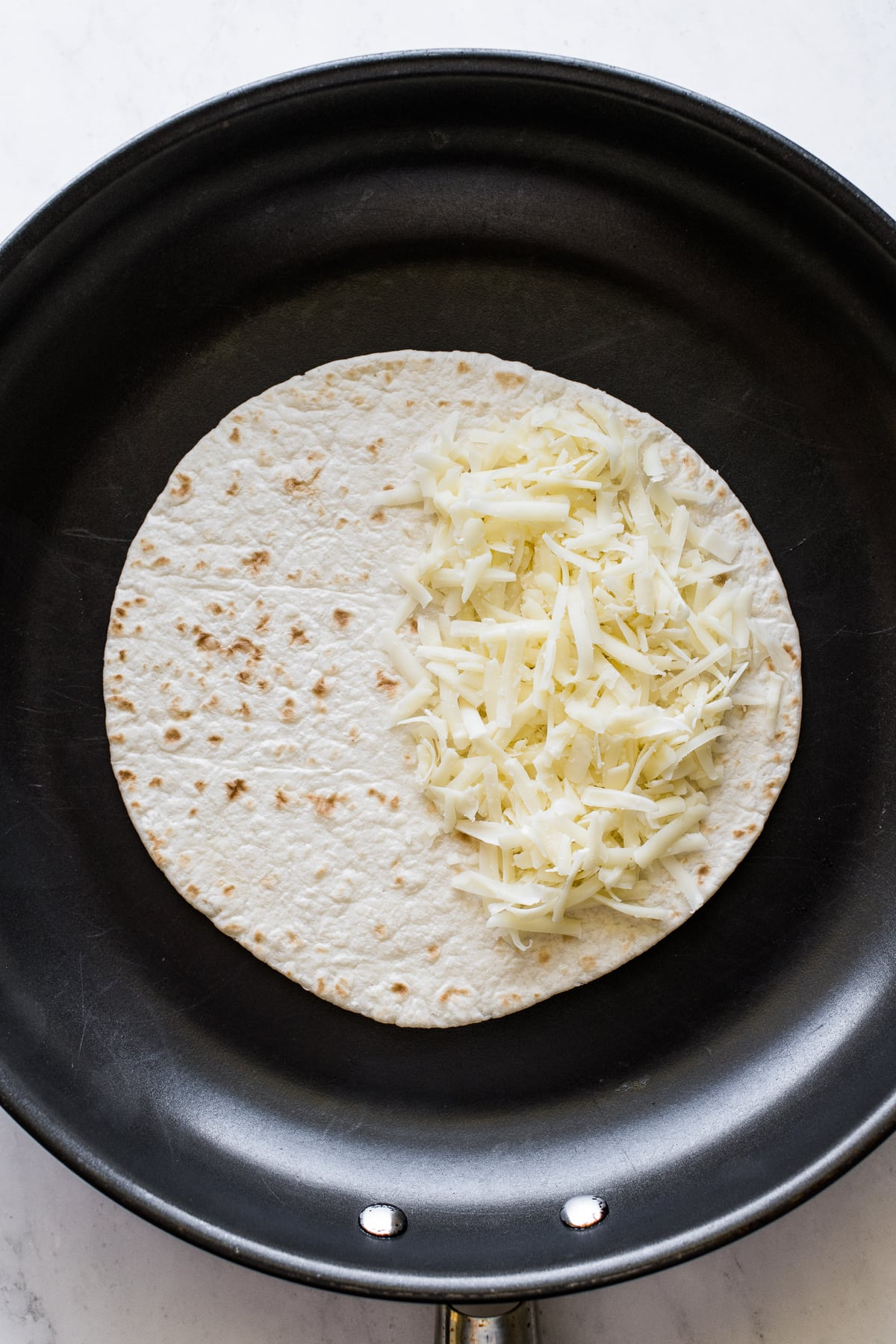 A flour tortilla in a skillet with shredded cheese.