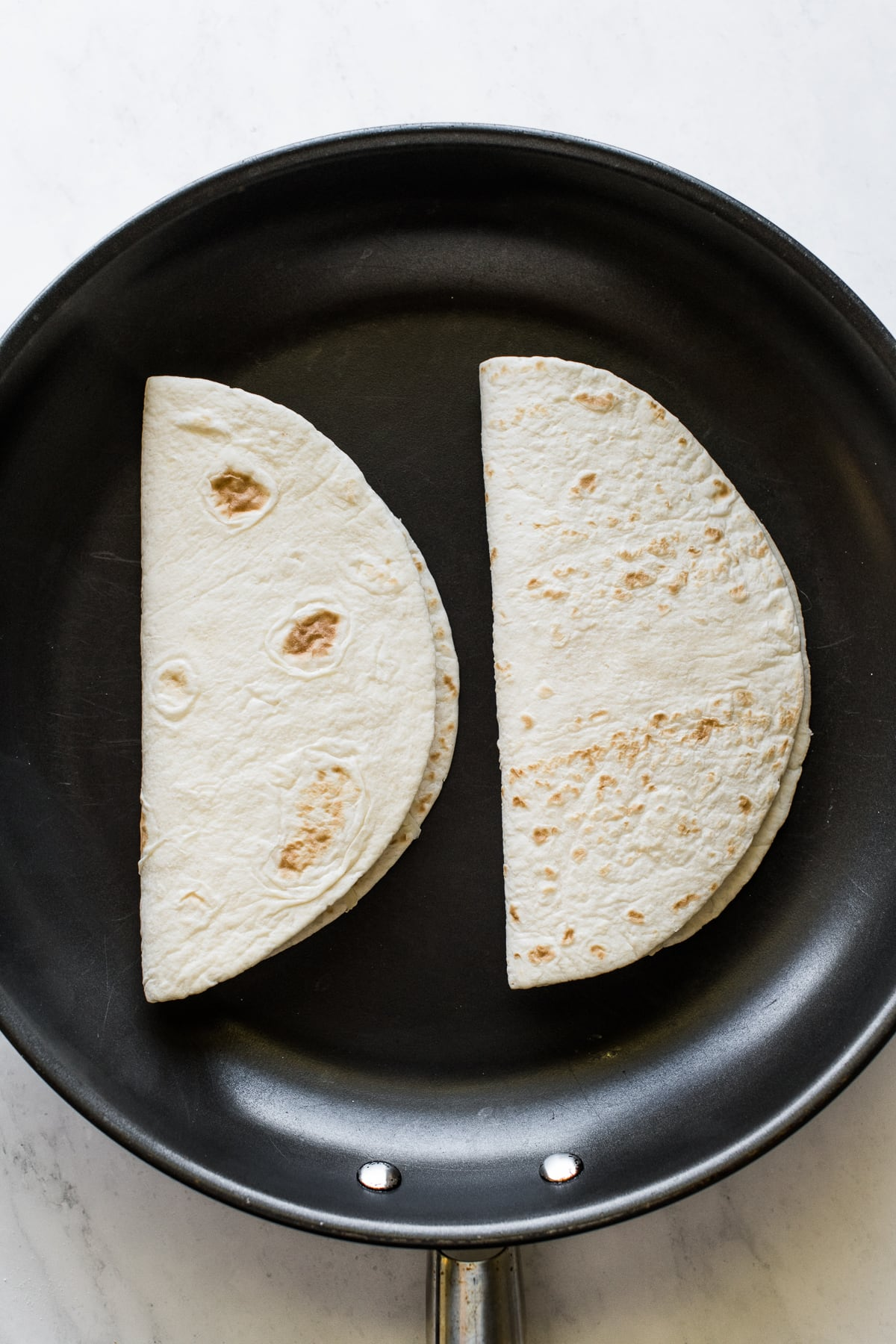 Two cheese quesadillas cooking on a skillet.