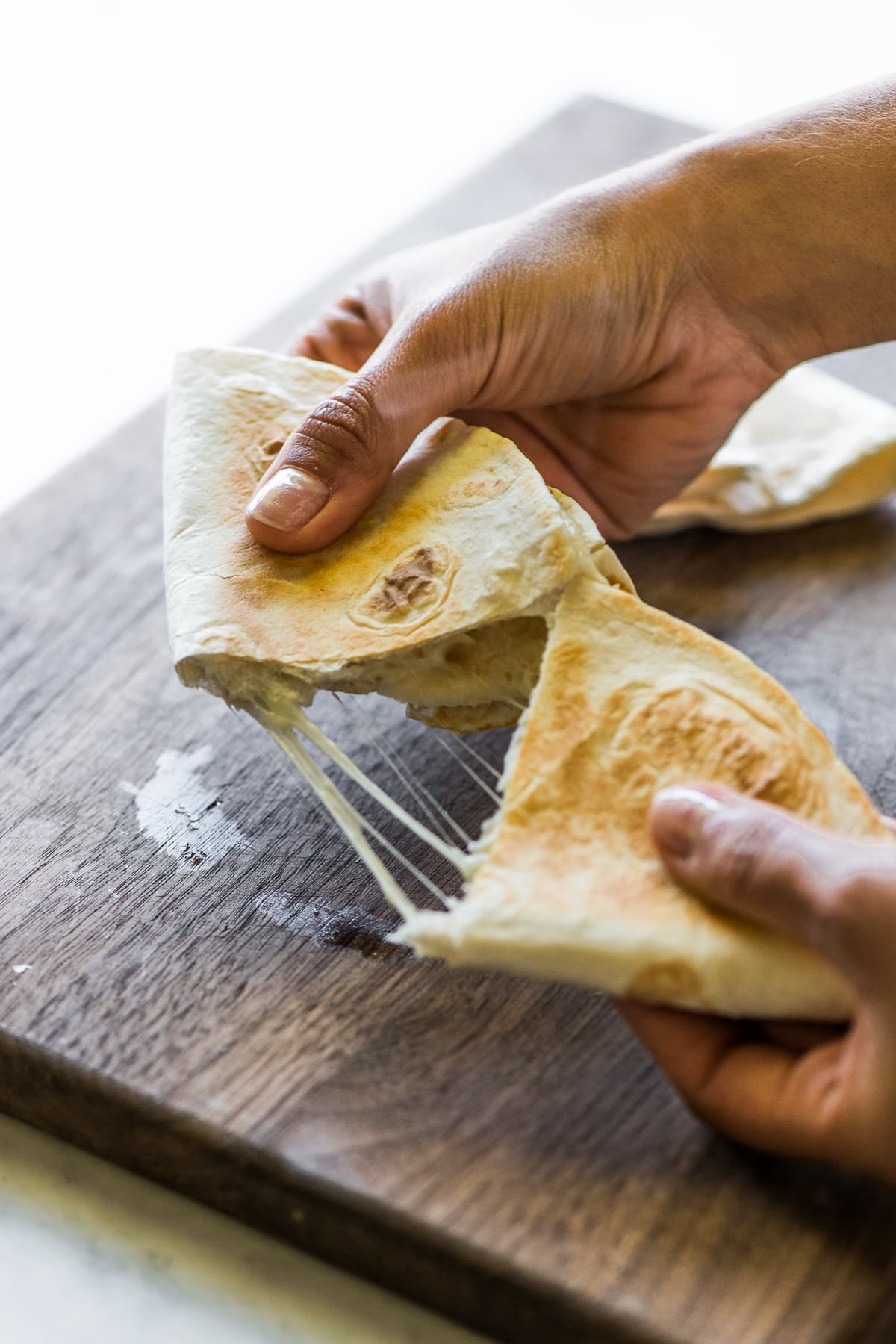 A cheese quesadilla being pulled apart, revealing melted stretchy cheese.