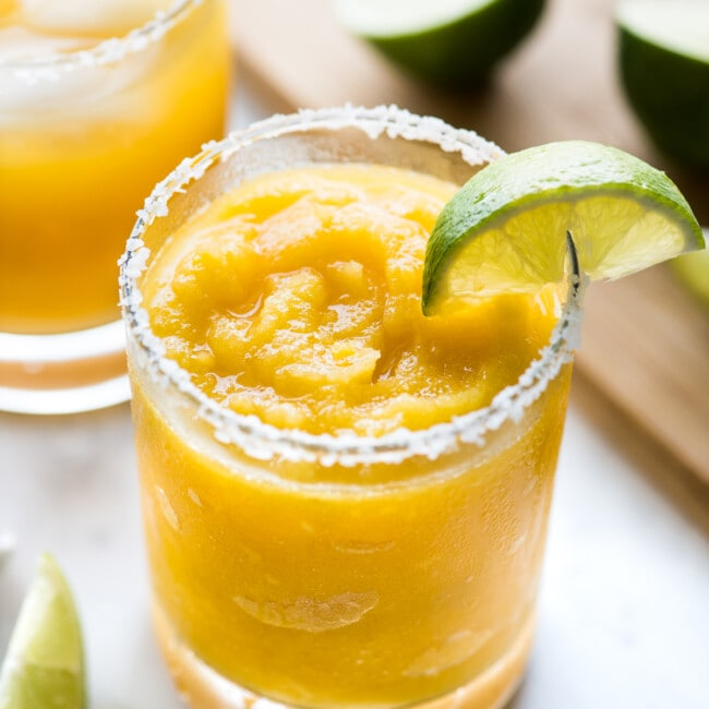 A mango margarita served frozen with a lime wedge.