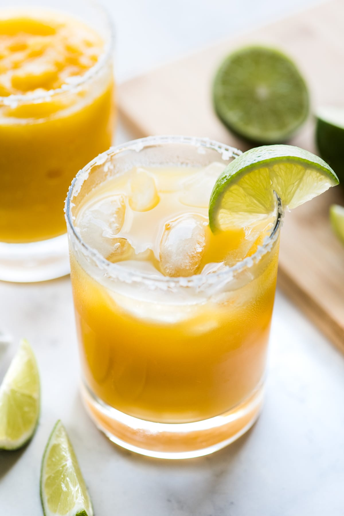 A mango margarita on the rocks with a lime wedge