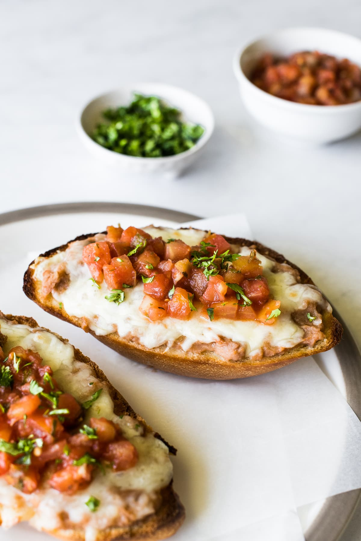 Molletes on a plate topped with pico de gallo.