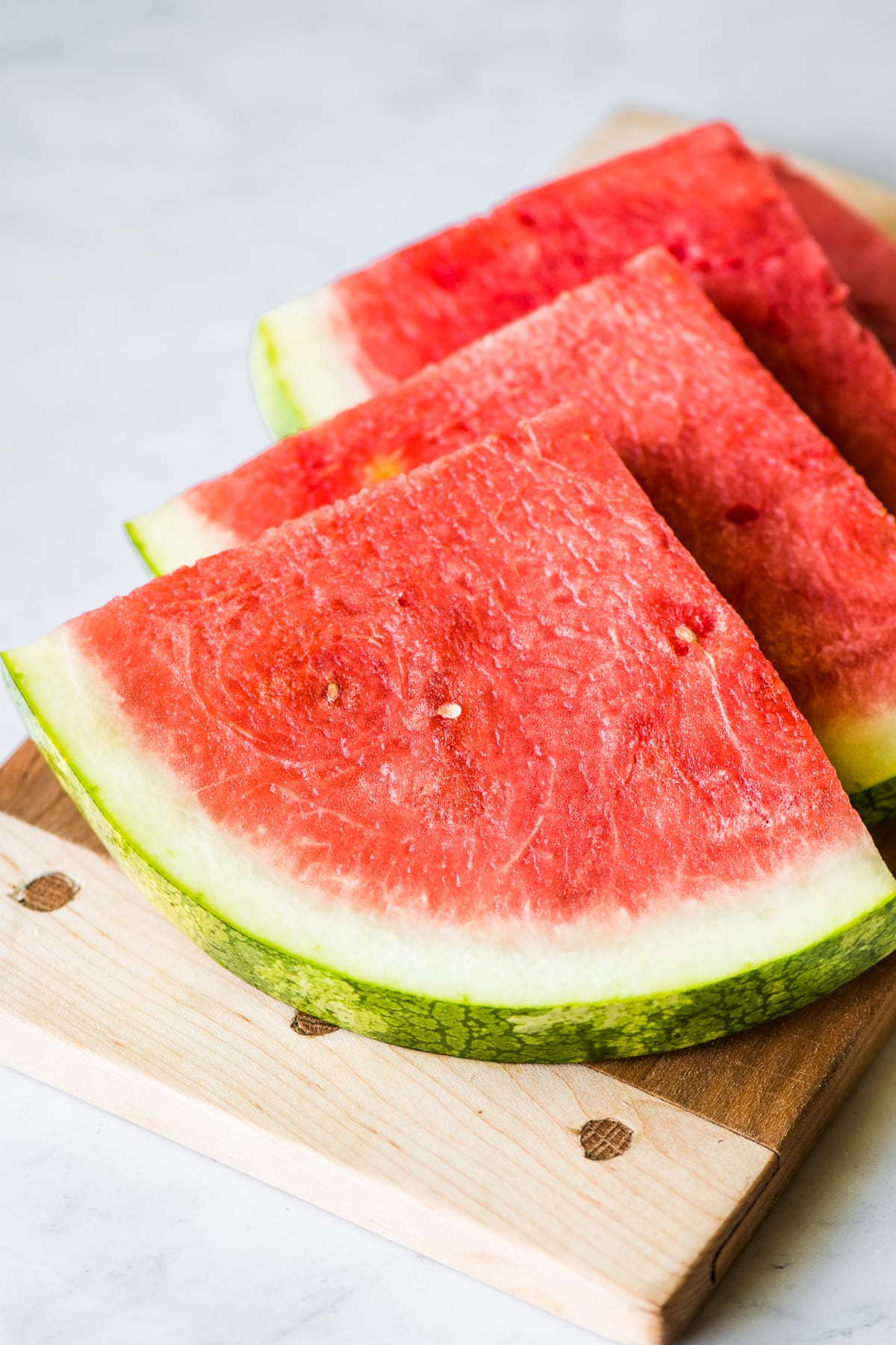 Slices of fresh watermelon on a cutting board.