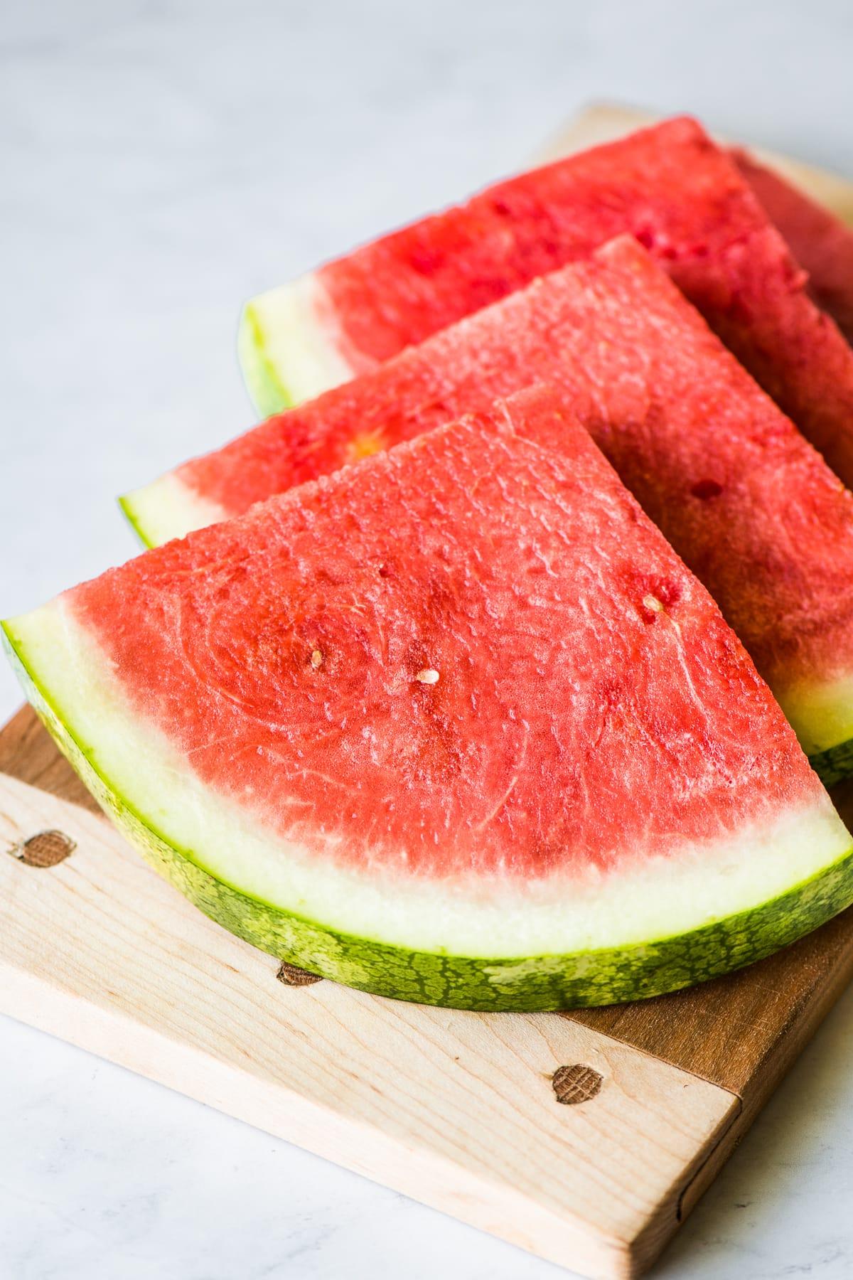 Slices of fresh watermelon on a cutting board.