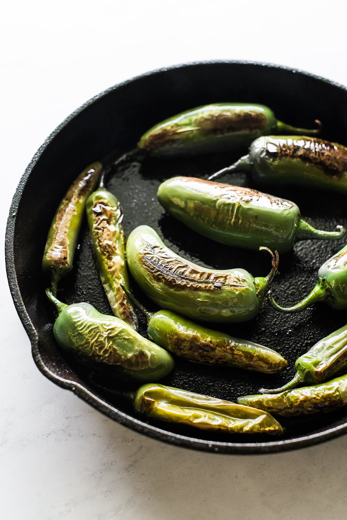 Jalapeno peppers in a skillet to make chiles torreados