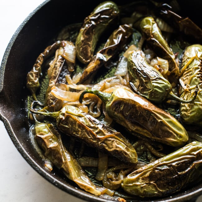 Chiles toreados in a skillet.