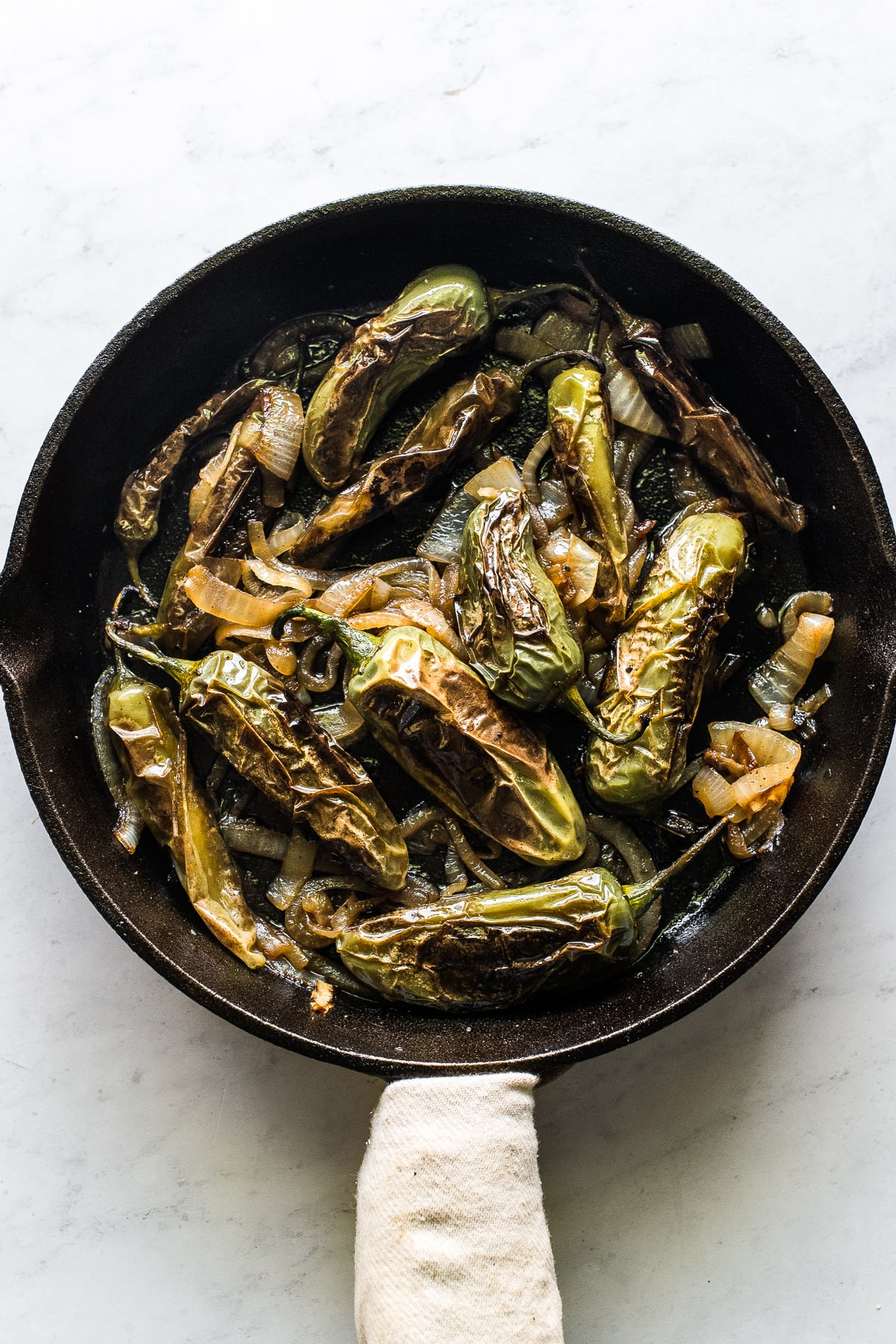 Chiles toreados in a cast iron skillet.