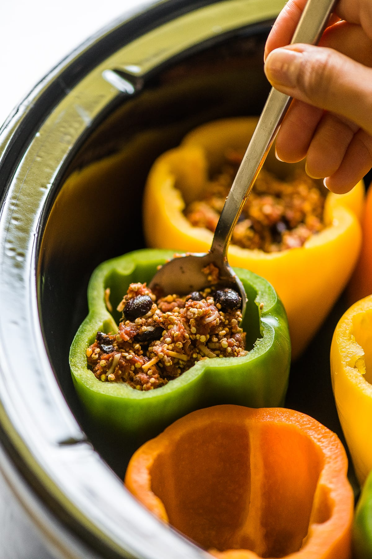 Bell peppers being stuffed with filling in a slow clooker.