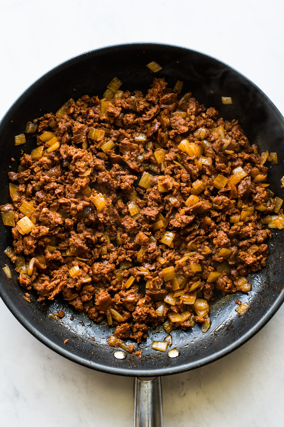 Cooked chorizo and onions in a skillet.